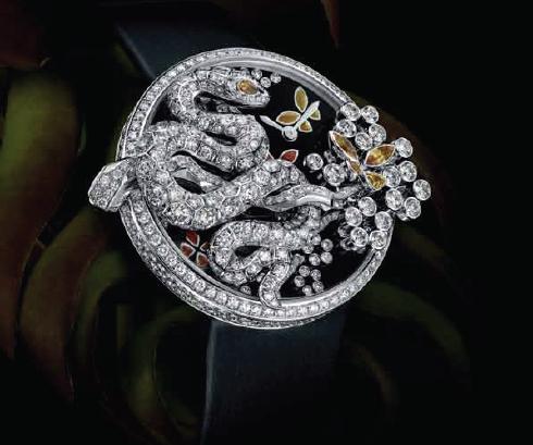 Es un broche, una serpiente de diamantes que se engancha a la carátula de esmalte negro de un reloj paisaje con flores y mariposas de granate.